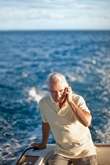 Mature man talking on cell phone while sitting at back of boat.