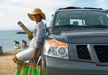 Woman leaning against car holding beach gear.