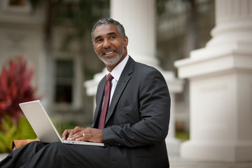 Smiling businessman using a laptop computer.