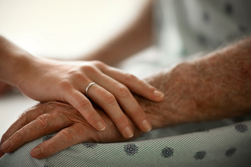 Young woman comforting an elderly man in the hospital.