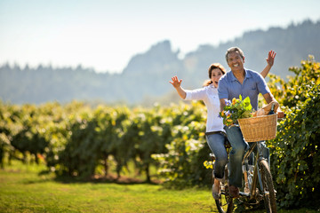 Middle-aged woman having fun riding the bicycle with her husband in the vineyard.