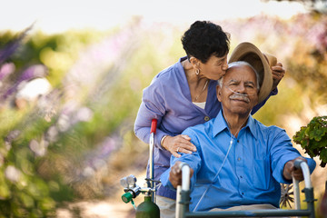 Happy senior man in a wheelchair being kissed on the head by his wife in a garden.