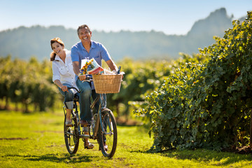Happy mature couple riding their double bicycle through the vineyard.