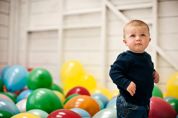 Little boy standing in a room full of balloons.