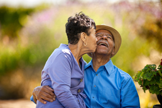 Senior woman kissing her happy husband.