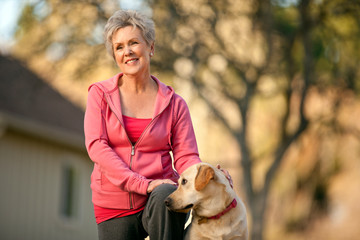 Smiling senior woman petting her dog outdoors.