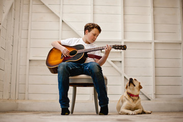 Boy sitting in a shed playing guitar with his dog by his side.