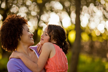 Mid adult woman grinning at her daughter as she holds her in the forest.