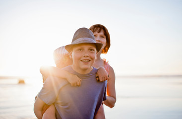 Teenage boy giving his younger brother a piggy back ride on a beach.