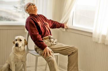 Laughing senior man sitting inside a room with his dog.