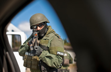 Mid adult army soldier aiming a gun while wearing a protective helmet.
