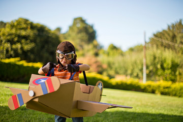 Young boy having fun pretending to be a pilot in a cardboard plane.