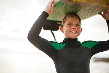 Portrait of a young boy with a surfboard.