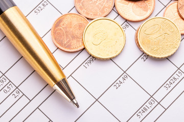 Stack of euro euro coins on old black wooden table. Pen and accounting documents with numbers