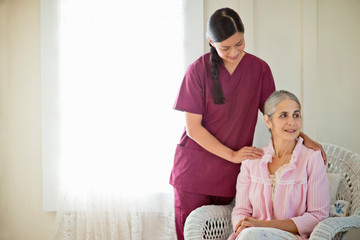 Smiling young nurse comforting an elderly woman.