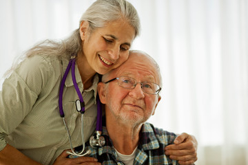 Doctor standing with her arms around an elderly patient.
