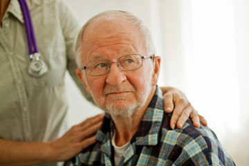 Elderly patient being comforted by a female doctor.