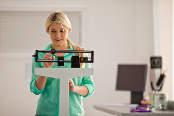 Smiling young woman concentrating as she adjusts the slide on a medical weight scale while inside a doctor's office.