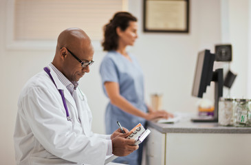 Male doctor taking notes on a clipboard as he holding a box of medication while in his office with a nurse.