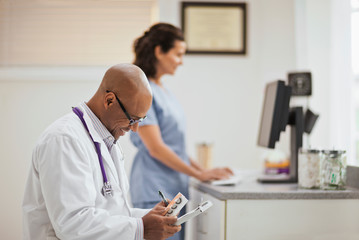 Smiling male doctor taking notes on a clipboard as he holding a box of medication while in his office with a nurse.