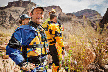 Portrait of a smiling mid adult man wearing a life vest while standing with friends in a rural landscape.
