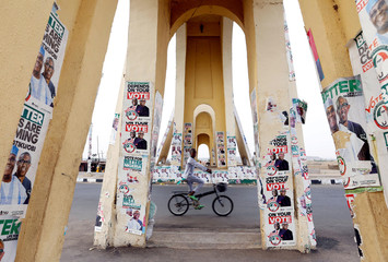 A boy rides a bicycle past a monument decorated with election posters depicting Nigeria's main opposition party presidential candidate Atiku Abubakar with his running mate, Peter Obi, in Yola