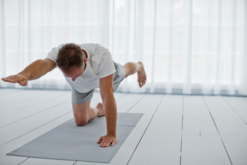 Middle aged man stretching his arms and legs while practicing yoga.