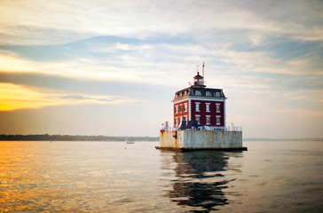 Lighthouse building surrounded by water.