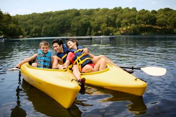 Happy family kayaking on a lake.