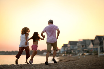 Couple and their young daughter holding hands and running on the beach at sunset.