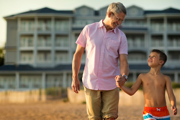 Father smiling and talking with his young son as they hold hands and walk on the beach at sunset.