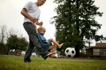 Smiling father teaches his little girl how to kick a soccer ball on the lawn.
