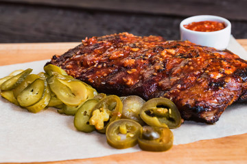 Close up roasted pork ribs with spices, jalapeno and ketchup on wooden board