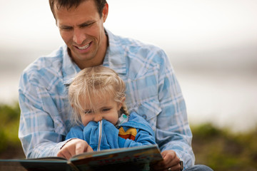 Smiling father enjoys reading a storybook to his little girl.