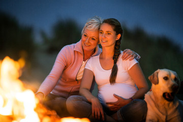 Happy mature woman and her pregnant daughter spend time together enjoying a beach bonfire at night.
