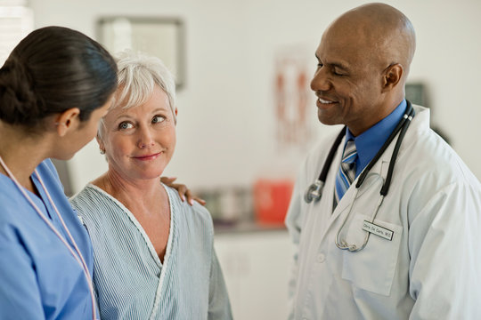 Smiling doctor talking with patient in hospital