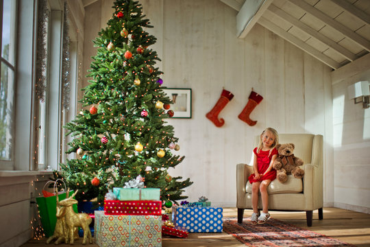 Young girl sitting on an armchair with her teddy bear, next to a Christmas tree.
