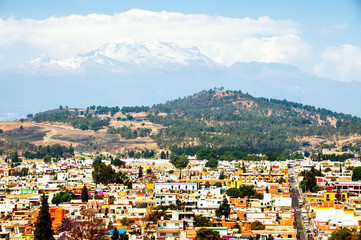 Aerial view of Cholula, Mexico with snowy mountains at the background