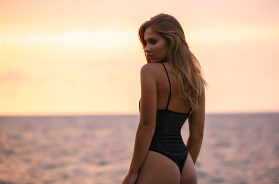 Sexy girl in black swimsuit at sunset