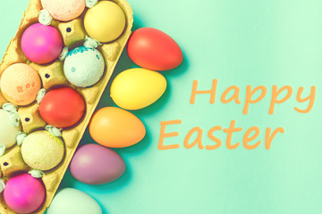 Bright Easter eggs lie in a box on a blue background. Inscription happy easter. Space for text. Easter ideas. Toned image.