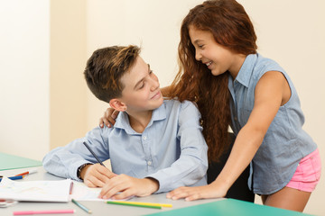 Handsome boy sitting at desk, looking at girl, embracing his shoulders in classroom.