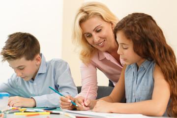 Schoolchildren studying drawing at school with pretty female teacher.