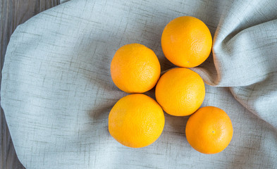 a group of ripe oranges in a beige linen cloth on a wooden table with copy space