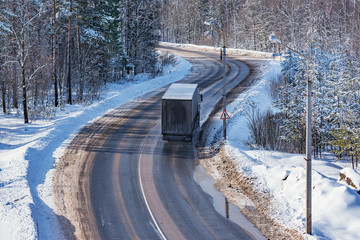 Freight truck moves on the road at winter day time.