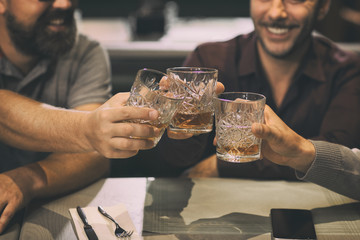 Close up of unrecognizable men clinking crystal glasses with alcoholic beverage. Clients of bar or pub enjoying their drinks such as whiskey, rum, scotch or brandy.