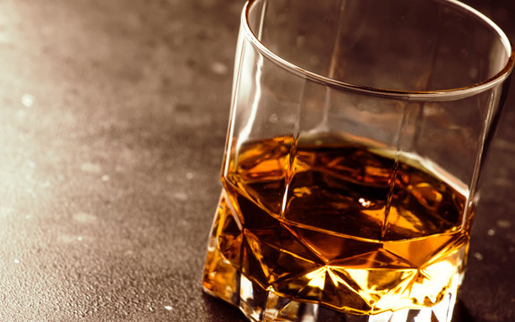 One glass of golden scotch whiskey on dark old bar table background, selective focus