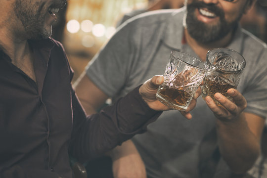 Close up of two unrecognizable men clinking crystal glasses with strong alcohol. Bearded men smiling and laughing. Concept of elite alcohol, scotch, brandy and whiskey.