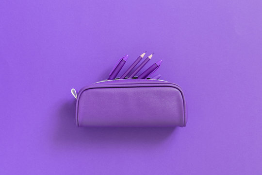 Purple school supplies in pencil case on background of purple paper. Back to school background. Flat lay, top view, copy space