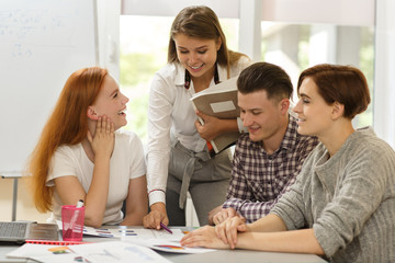 Professional smiling teacher showing notes and explaining new material while students sitting at...