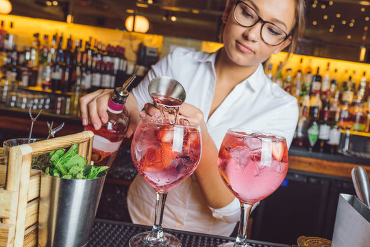 female beautiful smart bartender mixologist bar person makes prepares gin tonic cocktail drink pink mint fish bowl glass